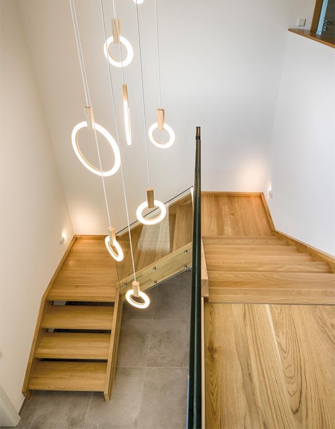 Holztreppe mit Glasgeländer und Lichtelementen